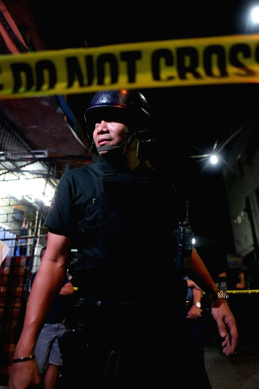 MANILA, May 6, 2017 - A policeman secures the area where twin blasts occurred in Manila, the Philippines, on May 6, 2017. Two people were killed and four others injured, including a policeman, in ...
