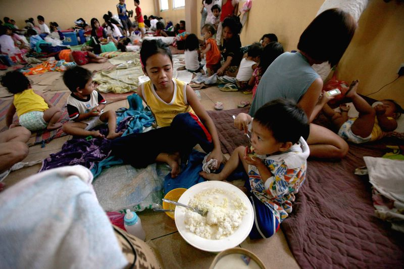 Manila (Philippines): Residents eat inside an evacuation center due to strong winds and heavy rains brought by typhoon Hagupit in Manila, the Philippines, Dec. 8, 2014. Typhoon Hagupit is packing ...