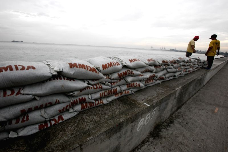 Manila (Philippines): Workers reinforce a seawall with sandbags bracing for the strong winds and heavy rains brought by typhoon Hagupit in Manila, the Philippines, Dec. 8, 2014. Typhoon Hagupit is ...