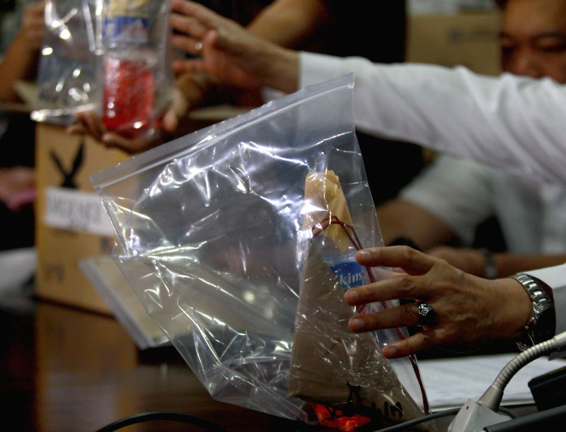 A staff member of National Bureau of Investigations (NBI) holds bags of alleged homemade bombs at the NBI headquarters in Manila, the Philippines, Sept. 2, 2014. The