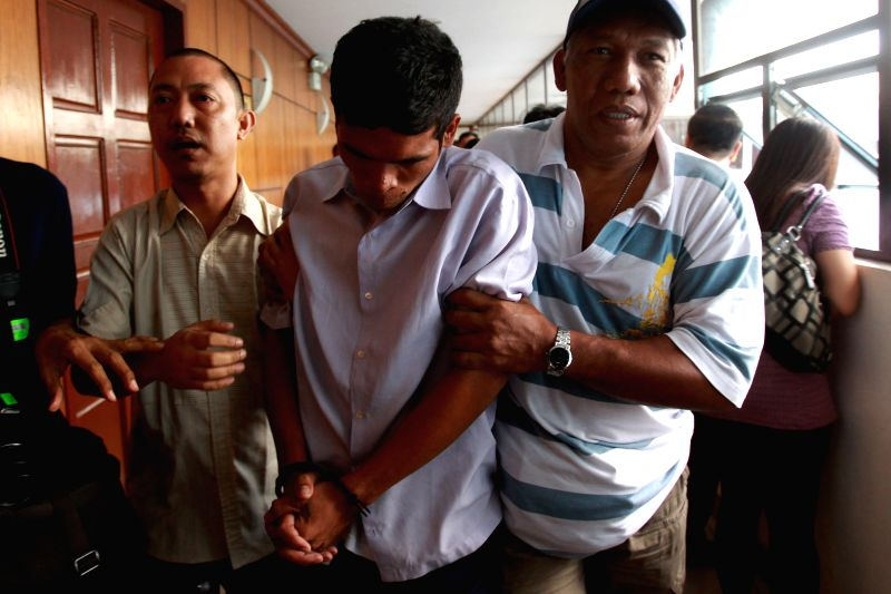 Operatives from the National Bureau of Investigations (NBI) escort one of the three suspected bombers at the NBI headquarters in Manila, the Philippines, Sept. 2, ...