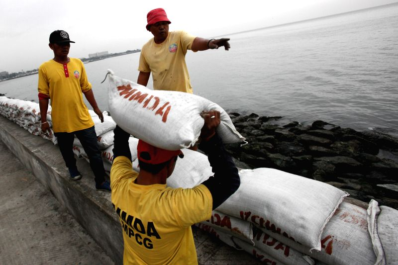 Workers reinforce a seawall with sandbags bracing for the strong winds and heavy rains brought by typhoon Hagupit in Manila, the Philippines, Dec. 8, 2014. Typhoon Hagupit is packing maximum .