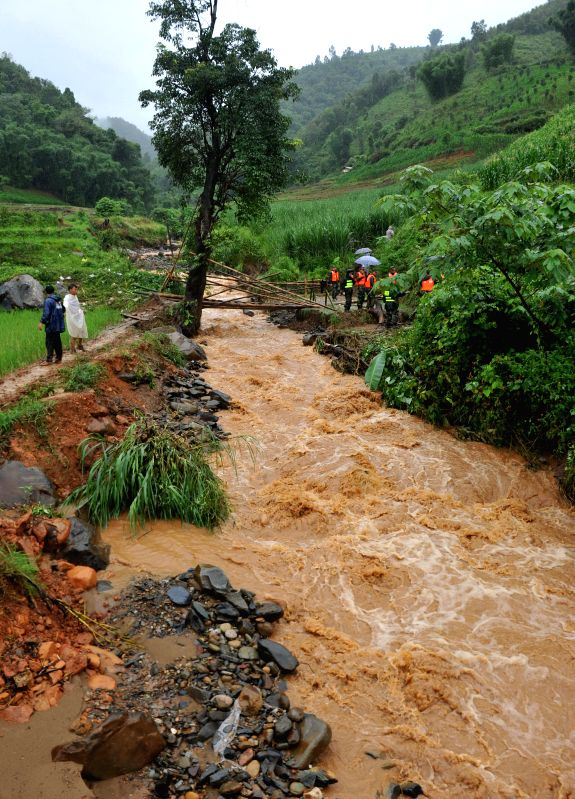 Rescuers set up a temporary bamboo bridge at Manghai Town in Dai-Jingpo Autonomous Prefecture of Dehong, southwest China's Yunnan Province, July 22, 2014. A mudslide