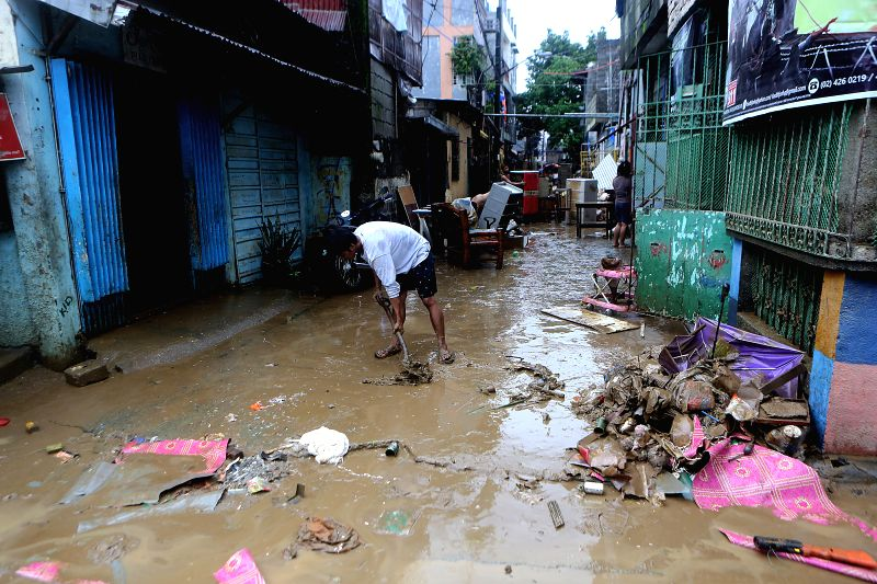 MARIKINA CITY , Aug. 12, 2018 - A resident cleans the lane after the flood in Marikina City, the Philippines, Aug. 12, 2018. Tropical storm Yagi enhanced the monsoon causing continous rain and ...