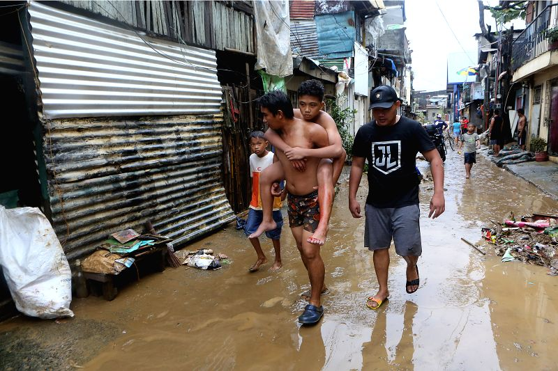 MARIKINA CITY , Aug. 12, 2018 - A wounded man is carried by another resident after the flood in Marikina City, the Philippines, Aug. 12, 2018. Tropical storm Yagi enhanced the monsoon causing ...