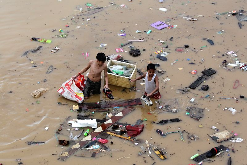 MARIKINA CITY, Aug. 12, 2018 - Kids wade through the flood brought by tropical storm Yagi as they look for their belongings in Marikina City, the Philippines, Aug. 12, 2018.