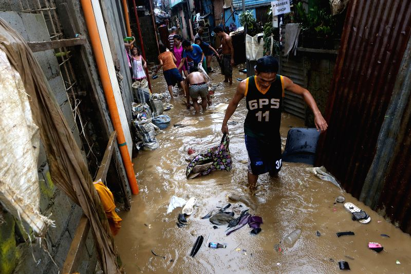 MARIKINA CITY , Aug. 12, 2018 - Residents clean mud and debris after the flood in Marikina City, the Philippines, Aug. 12, 2018. Tropical storm Yagi enhanced the monsoon causing continous rain and ...