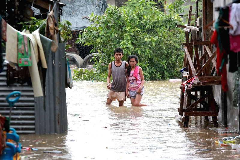 MARIKINA CITY, July 22, 2018 - Residents stand in flood water brought by heavy rains in Marikina City, the Philippines, July 22, 2018. At least five people died and more than 700,000 were affected by ...