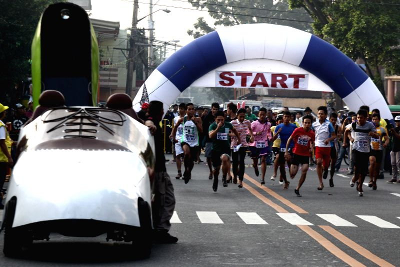 "Marikina City: Men wearing high-heeled shoes run during the ""Tour de Takong"" (Tour of High Heels) in Marikina City, the Philippines, on Nov. 13, 2014. Residents took part in the annual Tour"