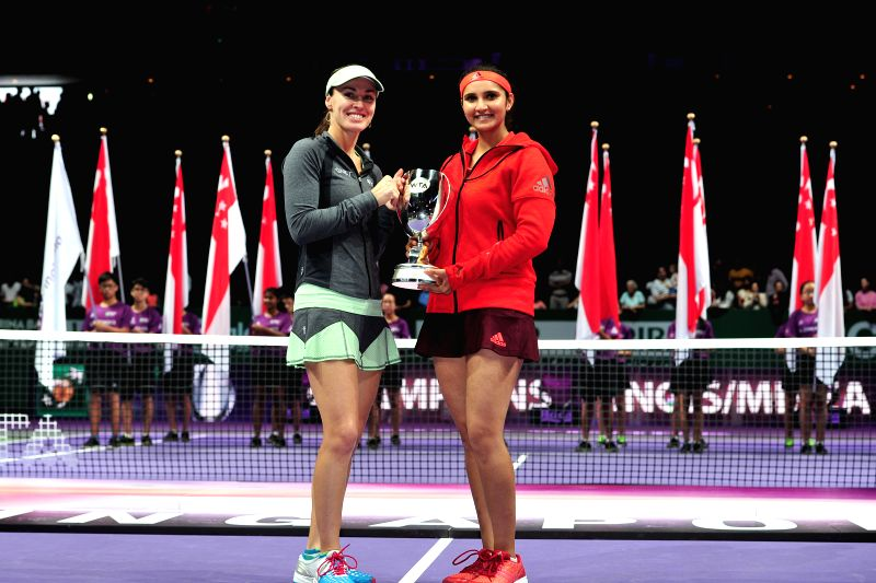 Martina Hingis (L) of Switzerland and Sania Mirza of India attend the awarding ceremony after winning WTA's women's doubles final match against Garbine Muguruza ... - Martina Hingis and Sania Mirza