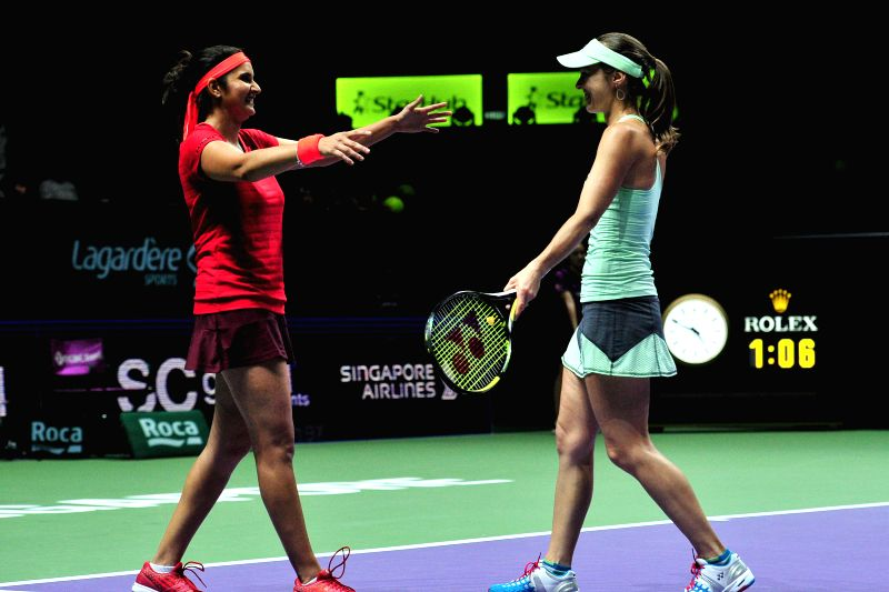 Martina Hingis (L) of Switzerland and Sania Mirza (C) of India celebrate after winning WTA's women's doubles final match against Garbine Muguruza and Carla Suarez ... - Martina Hingis and Sania Mirza