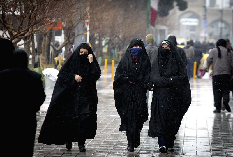 Iranian women walk on a street during a snowfall in downtown Mashhad, Iran, Jan. 23, 2015. A cold wave hit the city in recent days.