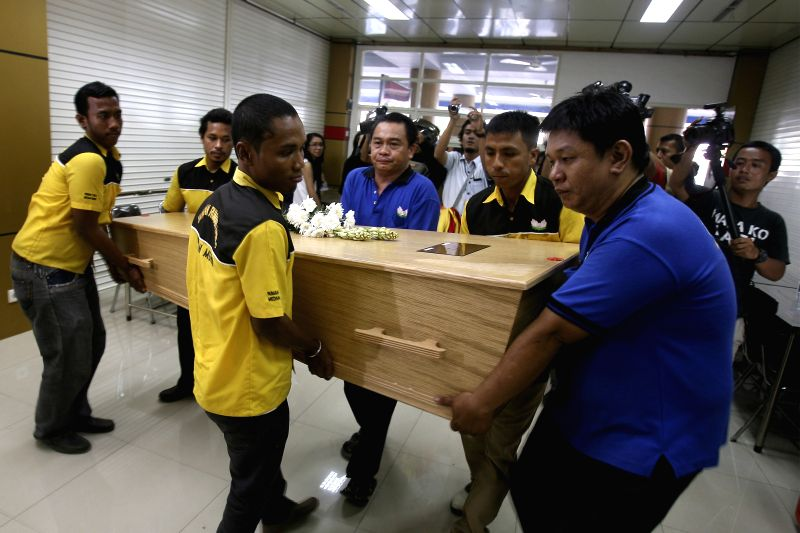 People carry the coffin of Hendry, a victim of Malaysia Airlines flight MH-17, as his body returns home in Medan, North Sumatra, Indonesia, Aug. 31, 2014. The ...