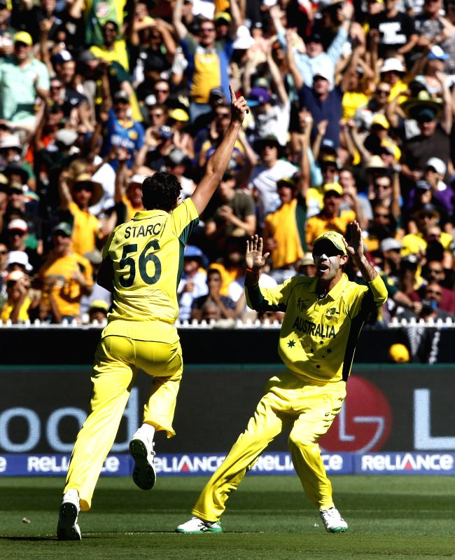 Melbourne (Australia): Australian cricketers celebrate fall of a wicket during the final match of ICC World Cup 2015 between Australia and New Zealand at Melbourne Cricket Ground in Australia on ...