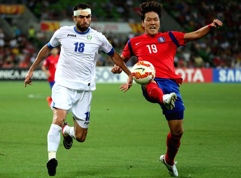 South Korea's Kim Young Gwon (R) fights for the ball with Uzbekistan's Timur Kapadze during the quarterfinal match at the 2015 AFC Asian Cup in Melbourne, ...