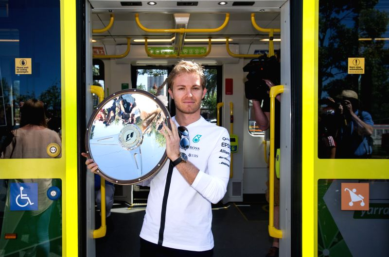 Formula One Australian Grand Prix Defending Champion Nico Rosberg of Germany poses with winner's trophy onboard an iconic Melbourne tram outside the Albert Park ...