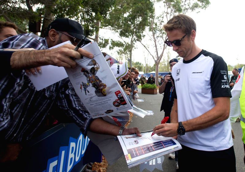 McLaren-Honda Formula One driver Jenson Button of Great Britain signs autographs for his supporters ahead of Australian Formula One Grand Prix at Albert Park in ...