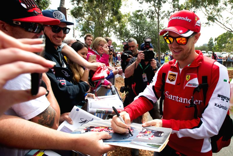 Scuderia Ferrari Formula One driver Sebastian Vettel of Germany signs autographs for his supporters ahead of Australian Formula One Grand Prix at Albert Park in ...