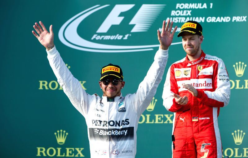 Scuderia Ferrari Formula One driver Sebastian Vettel of Germany reacts as Mercedes AMG Petronas Formula One driver Lewis Hamilton of Britain (L) celebrates after ...