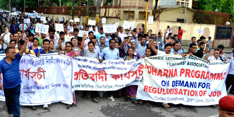 Members of All Assam Secondary Additional (Contractual) Teachers' Association (AASACTA) demonstrate to press for regularisation of their jobs in Guwahati on June 24, 2014.
