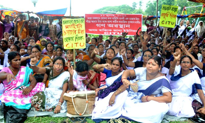 Members of Asom Raaijik Aasha Union (ARAU) affiliated to CITU stage a sit-in demonstration to press for hike in their salaries in Guwahati on July 11, 2014.