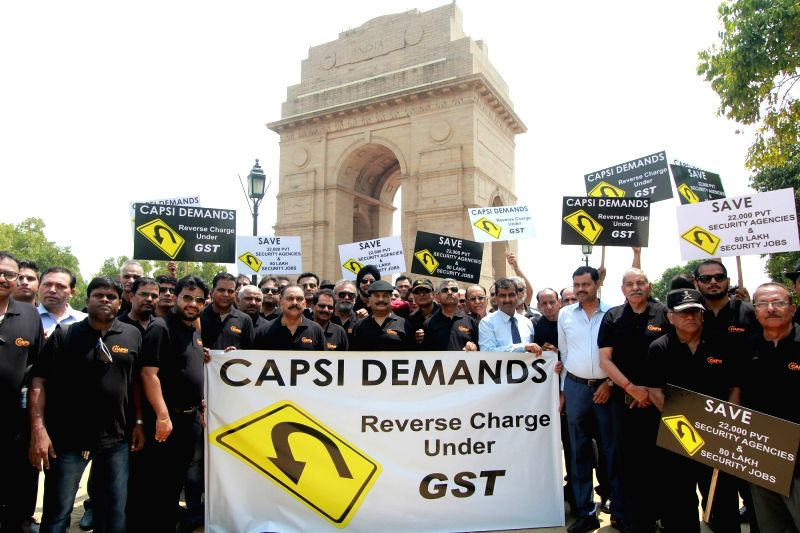 Members of Central Association of Private Security Industry (CAPSI) stage a demonstration to press for reverse charge under GST, at India Gate in New Delhi on July 18, 2018.