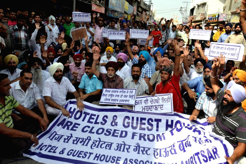 Members of  Hotels and Guest Houses Association demonstrate against administration's plan of sealing of illegal hotels in Amritsar on Aug 20, 2014.
