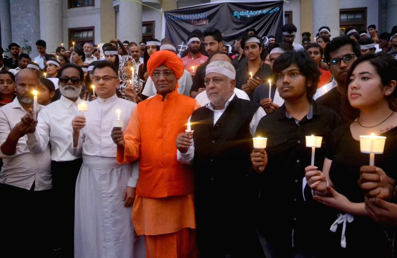 Members of Humanising India led by social activist Swami Agnivesh participate in a candle light protest rally against rape and atrocities on women organised by Humanising India, in ...