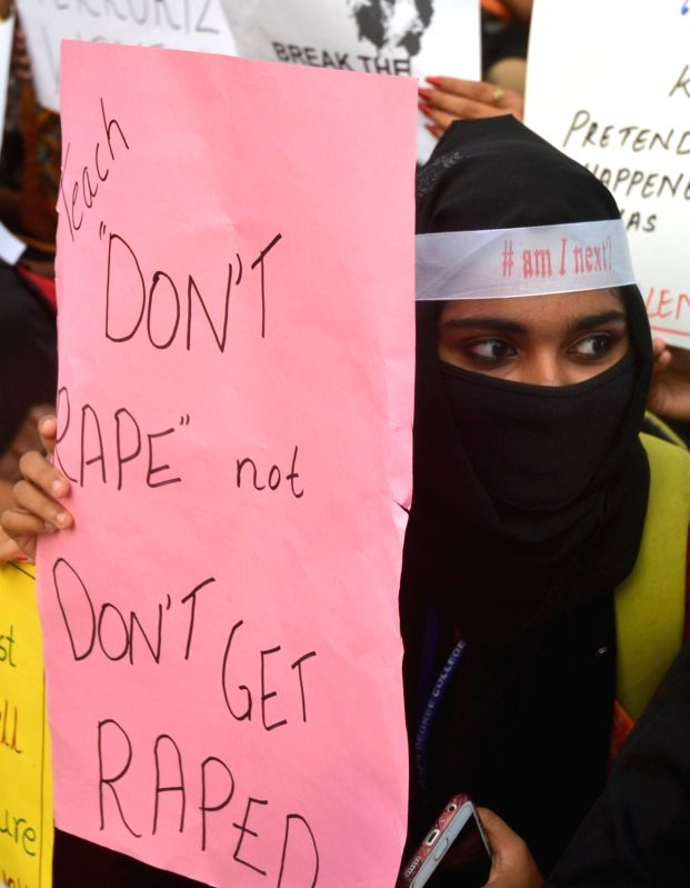 Members of Humanising India participate in a candle light protest rally against rape and atrocities on women organised by Humanising India, in Bengaluru on April 26, 2018.