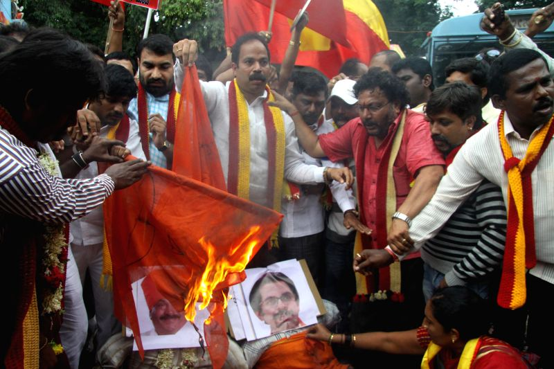 Members of Karnataka Rakshana Vedike led by Praveen Shetty seen burning the MES Flag, protesting against the MES MLAs attack on Kannadigas, the protest was held at SBM Circle, in Bangalore on August . - Praveen Shetty