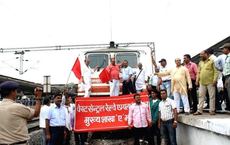 Members of West Central Railway Employees' Union demonstrate in front of  the engine of Shatabdi Express to press for their various demands in Bhopal on July 7, 2014.
