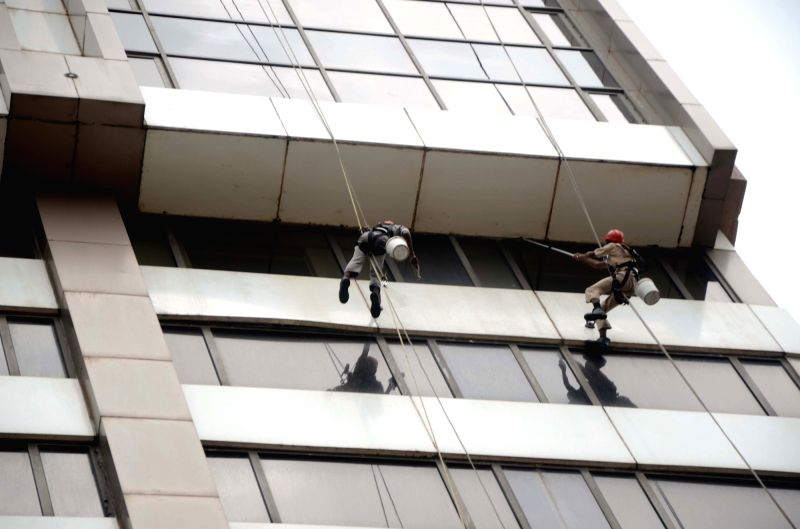 Men busy cleaning a exteriors of a Mumbai building on Aug 7, 2018.