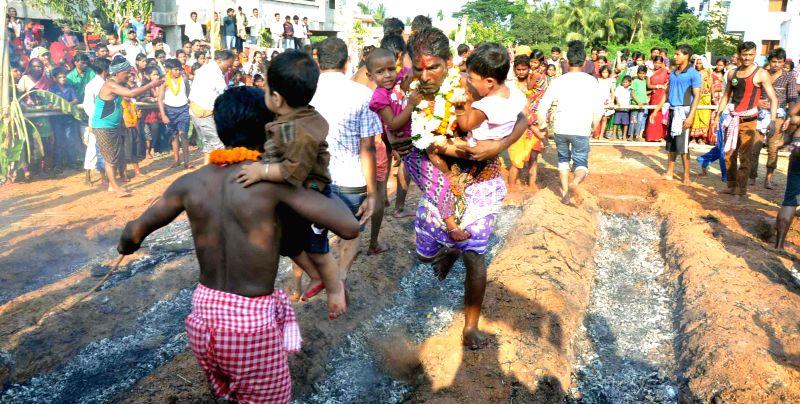 Men walk on burning charcoal during 'Jhamu Yatra' in Odisha on April 15, 2014. (Photo : Arabinda Mahapatra/IANS)