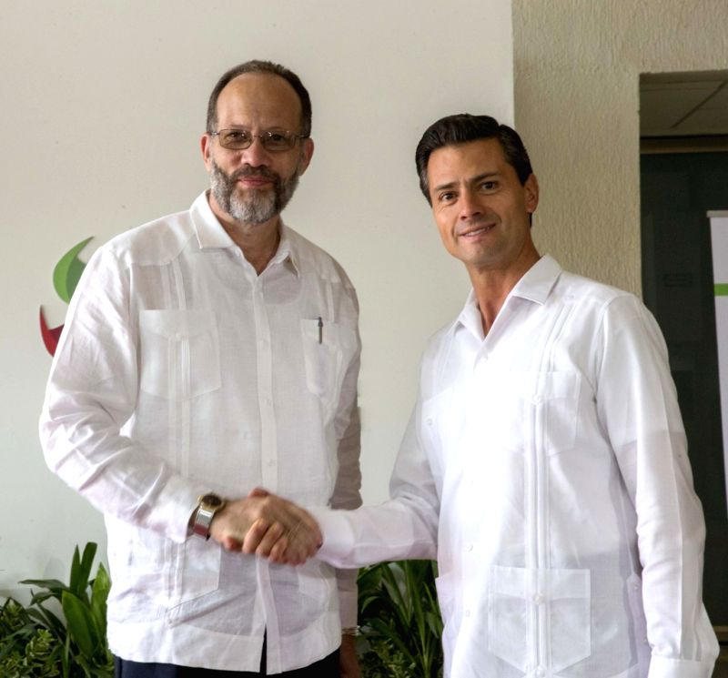 Image provided by Mexico's Presidency shows Mexican President Enrique Pena Nieto (R) shaking hands with Irwin LaRocque, secretary general of the Caribbean Community
