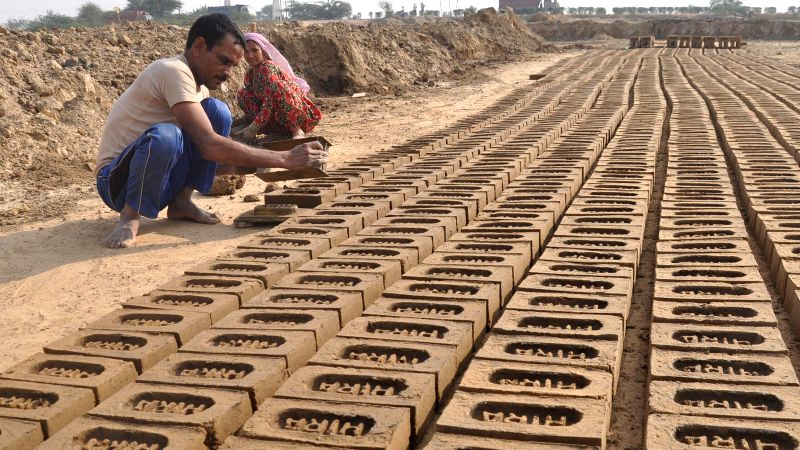 Daily-wagers busy working at a brick kiln in Mewat district of Haryana on Dec 3, 2014.
