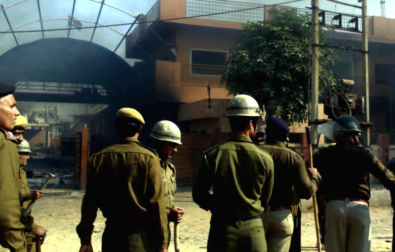 Policemen deployed at Rojka Meo village after the villagers torched an office of a company following the mysterious death of a worker in Mewat district of Haryana on Nov 30, 2014.
