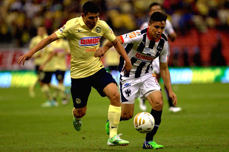 America's Luis Mendoza (L) vies with Efrain Velarde of Monterrey during the semifinal match of Opening Tournament of the MX League at Azteca Stadium in Mexico City, capital of Mexico, on Dec.