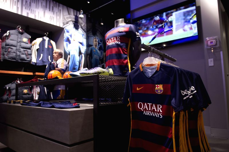 Mexico City: A man selects items of FC Barcelona during the opening of the official FC Barcelona store in Mexico City, capital of Mexico, on Dec. 10, 2015. Football club Barcelona opened its first ...