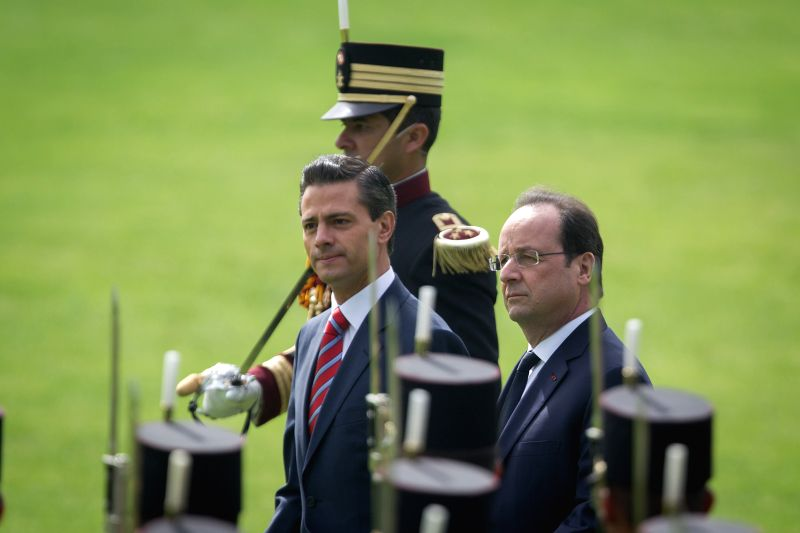 Mexican President Enrique Pena Nieto (front L), and French President Francois Hollande (R), take part in the official welcome ceremony for the French leader, ..