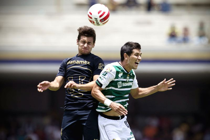 UNAM's Pumas Kevin Escamilla (L) vies for the ball with Santos's Jesus Molina during the match of Closing Tournament of the MX League, held in the Olympic ...