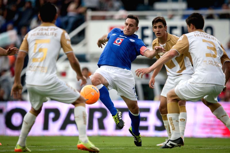 Christian Gimenez (C) of Cruz Azul vies for the ball with Josecarlos Van Rankin (2nd R) of UNAM's Pumas during their match of the MX League Closing Tournament
