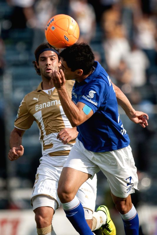 Fausto Pinto (Front) of Cruz Azul vies for the ball with Diego Lagos of UNAM's Pumas during their match of the MX League Closing Tournament held at Azul ...