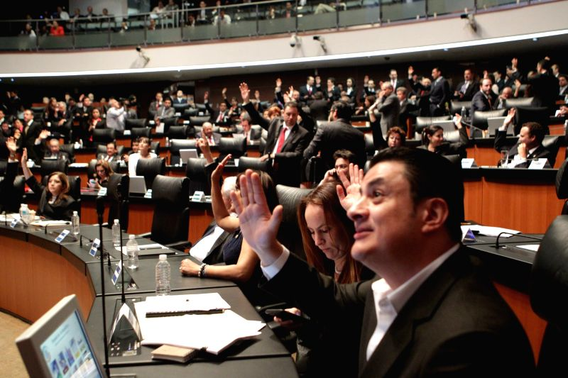 Senators take part in the vote of the political reform of the Federal District at the headquarters of the Republic's Senate, in Mexico City, capital of Mexico, ...