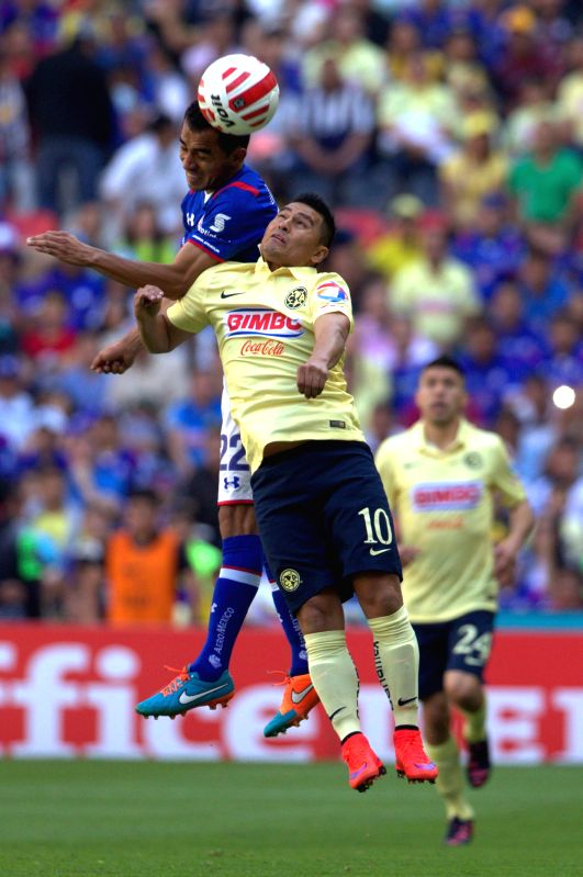 America's Osvaldo Martinez (bottom) vies the ball with Cruz Azul's Rafael Baca (up) during the match of the 2015 Closing Tournament of the MX League, in the ...