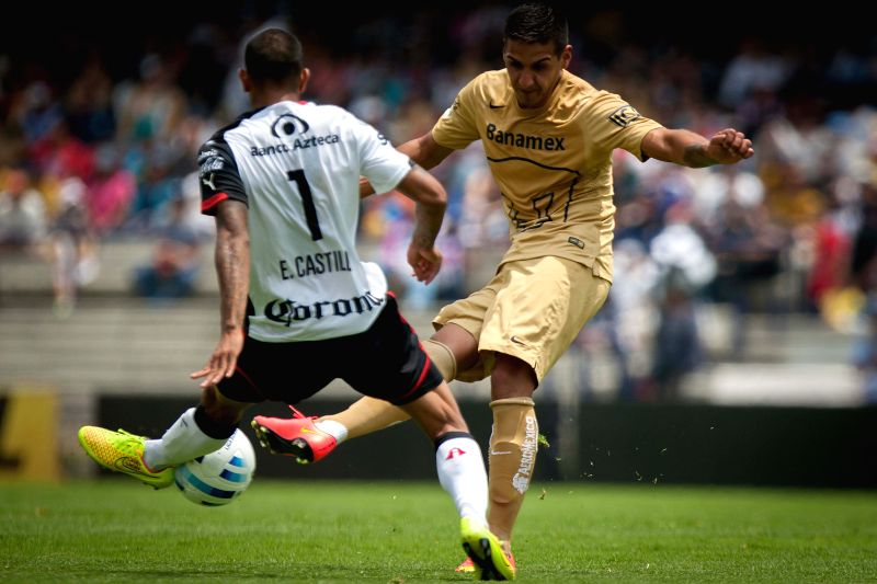 Ariel Sosa (R) of UNAM's Pumas vies for the ball with Edgar Castillo (L) of Atlas, during their match of the MX League Opening Tournament 2014, held at the ...