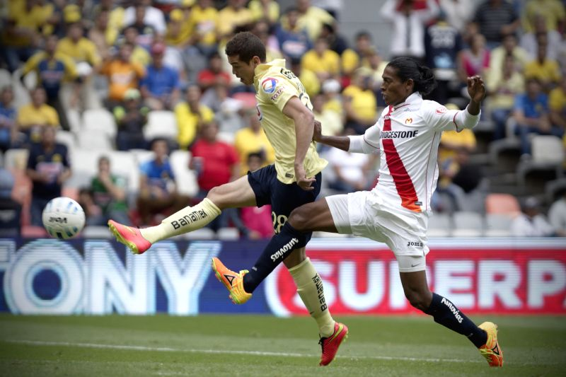 America's Martin Zuniga (L) vies for the ball with Morelia's Joel Huiqui, during their match of the MX League Opening Tournament held at Azteca Stadium in ...