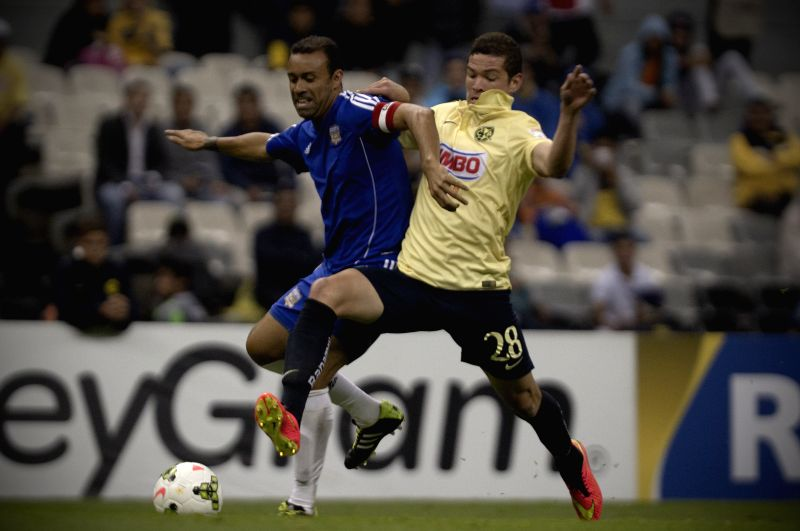 Martin Zuniga (R) of America of Mexico vies for the ball with Michael Rodriguez of Bayamon of Puerto Rico, during a CONCACAF 2014-2015 match, held in the Azteca
