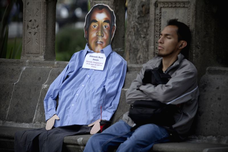 A man rests during a protest organized by relatives of missing persons and other organizations held in the framework of the International Day of the Disappeared