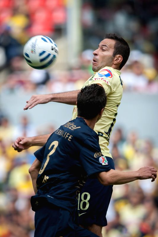 Luis Gabriel Rey (Back) of America vies for the ball with Marco Antonio Palacios of UNAM's Pumas, during their match of the MX League Opening Tournament 2014, ..