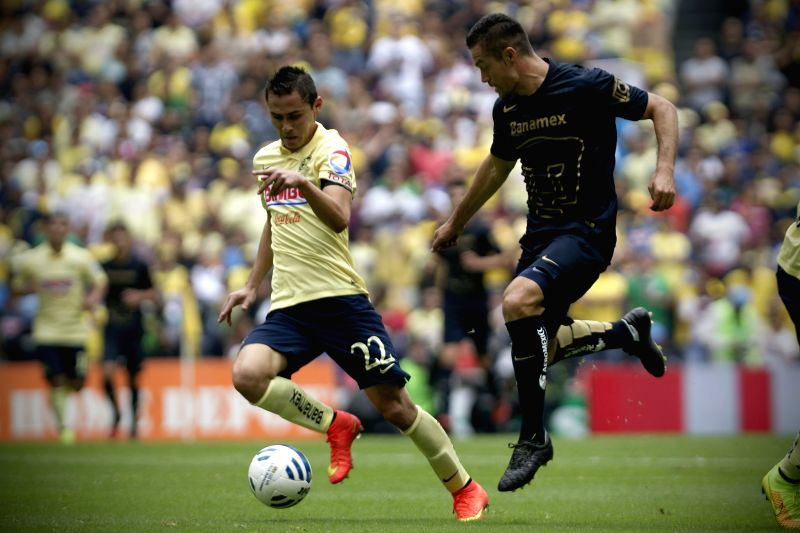 Paul Aguilar (L) of America vies for the ball with Dante Lopez of UNAM's Pumas during their match of the MX League Opening Tournament 2014, held at Azteca ...